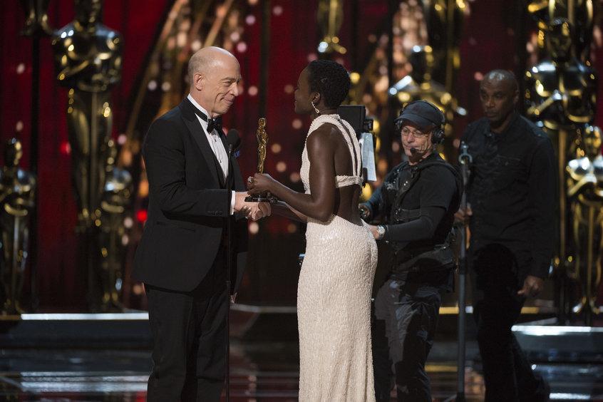 Дж.К.Симмонс получает награду из рук Люпиты Нионго. Фото с сайта oscar.go.com